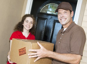 Friendly delivery man handing a package to a customer.  Focus on the man.